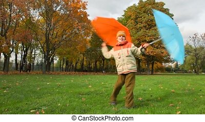 boy rotates with two umbrellas in autumn park