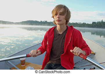 Boy Rowing Boat on Lake - Boy with red sweatshirt rowing a...
