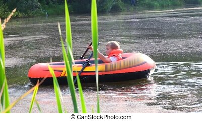 boy rowing on an inflatable boat across lake