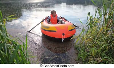 boy rowing on an inflatable boat away from coast