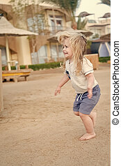 Boy run on sand barefoot