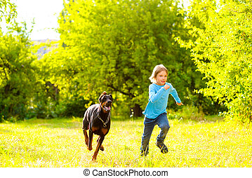 boy running away from dog or doberman in summer park
