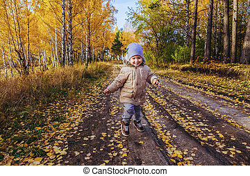 Boy running in the autumn forest