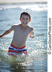 boy running into ocean