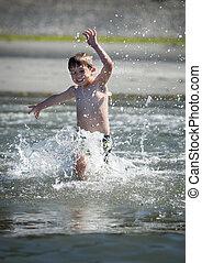 boy running into ocean