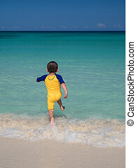 Boy running on beach into ocean