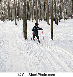 Boy running on skis in winter forest