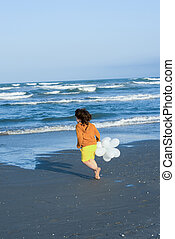Boy running on the beach with balloons