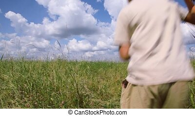 boy running through the field with airplane