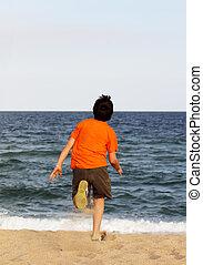 Boy running to the sea on summer holidays