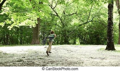 Boy runs across forest meadow all strewn fluff - Boy...