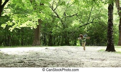 Boy runs closer across forest meadow all strewn fluff - Boy...