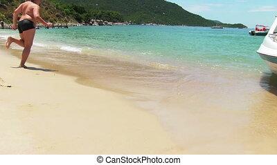 Boy runs into tropical sea