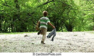 Boy runs, then he stops and runs back across meadow all...
