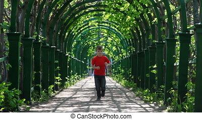 Boy runs through arched corridor braided green plants