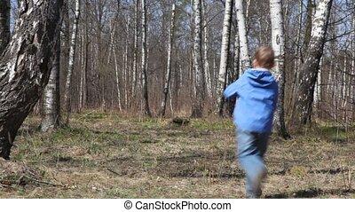 boy runs to spring brich grove from camera
