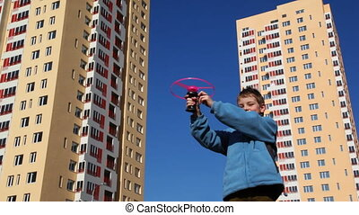 boy runs up toy helicopter against backdrop of high-rise...