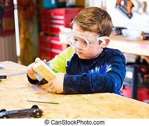 Boy sanding wooden block in workshop as he builds car for...