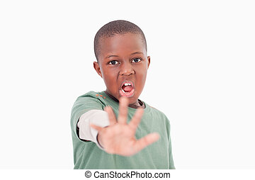 Boy saying stop with his hand against a white background