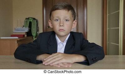 Boy schoolchild sitting in office at desk - A pupil in...