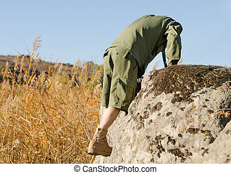 Boy Scout Climbing on a Big Rock at the Field