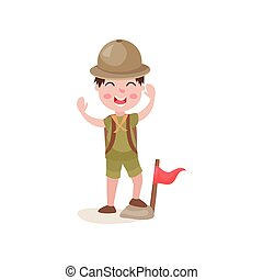 Boy scout standing with one foot on stone near flag and cheerfully waving his hands