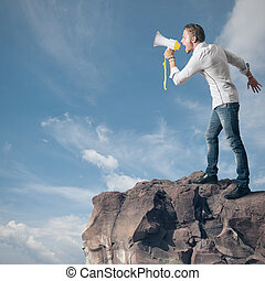 Boy screaming on the megaphone in the mountain