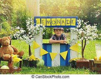 Boy Selling Yellow Lemonade at Stand - A little boy has an...