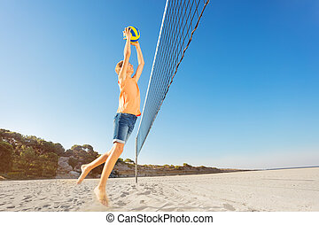 Boy serving the ball during beach volleyball game