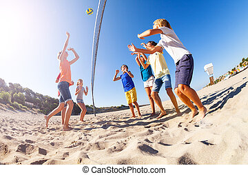 Boy serving the ball during beach volleyball match