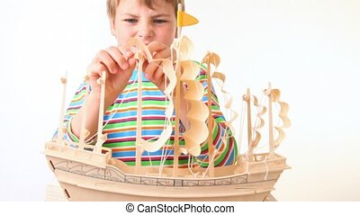 boy sets up sails of toy model of ship on white background