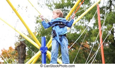 boy shakes suspended by rubber cords on in park attraction