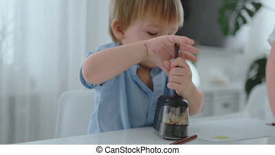 Boy sharpening a colored pencil in a sharpener sitting at the kitchen table.