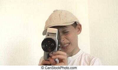 Boy shoots a film on 8mm movie camera