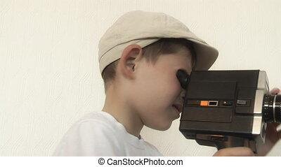 Boy shoots a film movie camera
