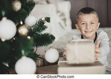 Boy showing a christmas present at camera