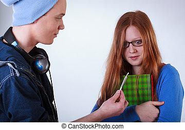 Naughty boy showing marijuana joint to calm student girl