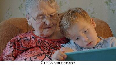 Boy Showing Something in Tablet to his Grandmother