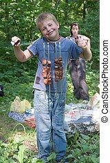 Boy shows freshly-fire shashlik on the spit