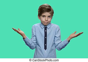 Boy shrugging shoulders against color background.