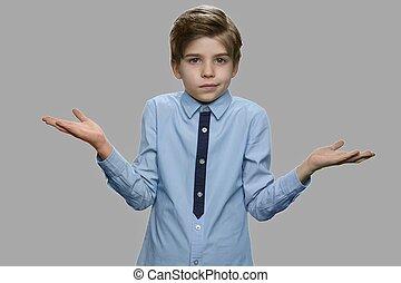Boy shrugging shoulders against gray background.