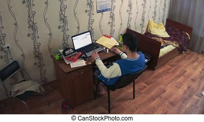 Boy sit at notebook in dormitory room. Almost lay on chair....