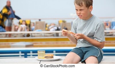 boy sits and eats pizza, washing down with water against people