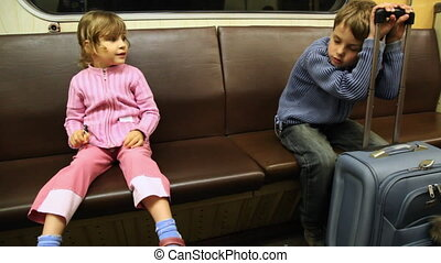 Boy sits and sleeps leaning to bag as well sister shows at him finger in riding subway train