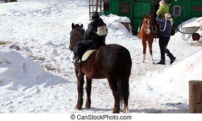 Boy sits horseback, woman help his sister to climb on horse