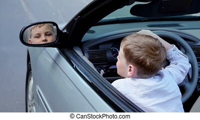 boy sits in car on driver place and watches in rear-view mirror