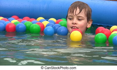 boy sits in inflatable water pool with balls