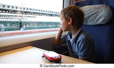 Boy sits, listens to ear-phone and looks out of window train during movement