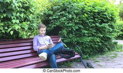boy sits on a bench and calling by mobile phone