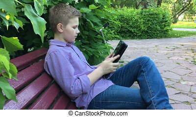boy sits on a bench and playing on the tablet